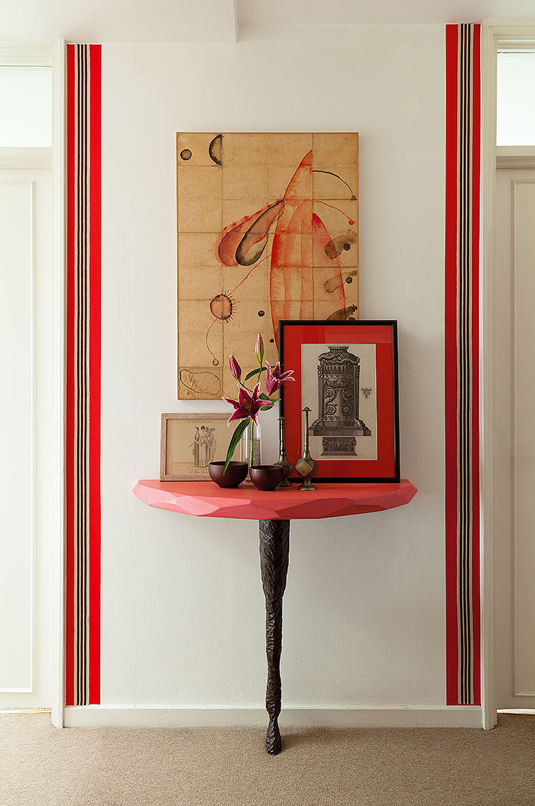 HALLWAY     To give the long, white corridor a bit of style, I added borders of red vinyl and striped webbing. I made the little console with a faceted, pink-lacquered top and a carved, bronzed camel's leg myself. On it, a Piranesi print and, above, a painting by James Brown.