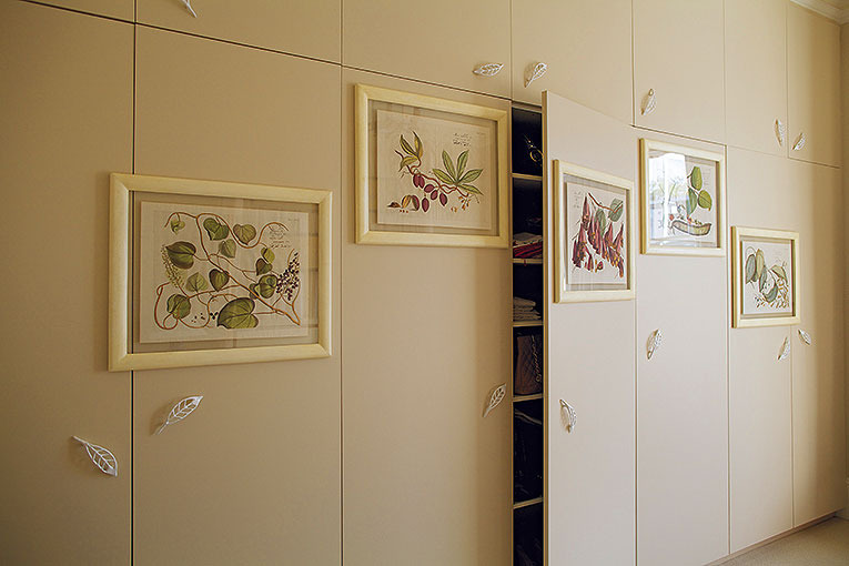BEDROOM WARDROBES Faced with an ugly wall of existing wardrobes, instead of changing them at great expense, I mounted these parchment-framed botanical drawings on the doors, with my Leaf handles in white enamel, scattered as though tumbling in a breeze.