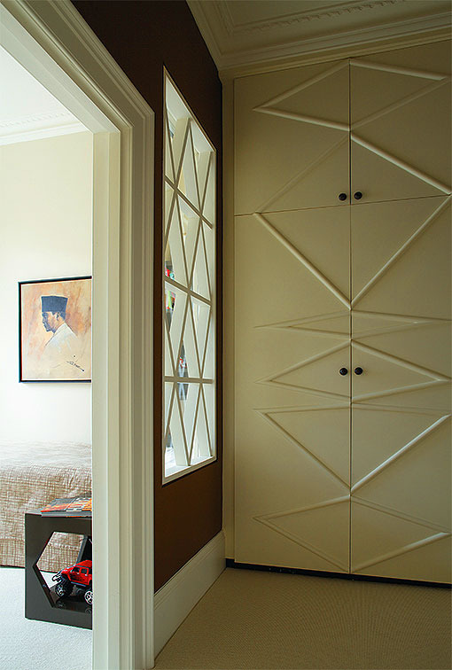 CHILD'S ROOM The internal window at the end of the hallway gives onto the owner's son's bedroom, with a hexagon-pierced cube bedside table. In the hallway, the linen cupboard doors have applied mouldings in a random geometry.