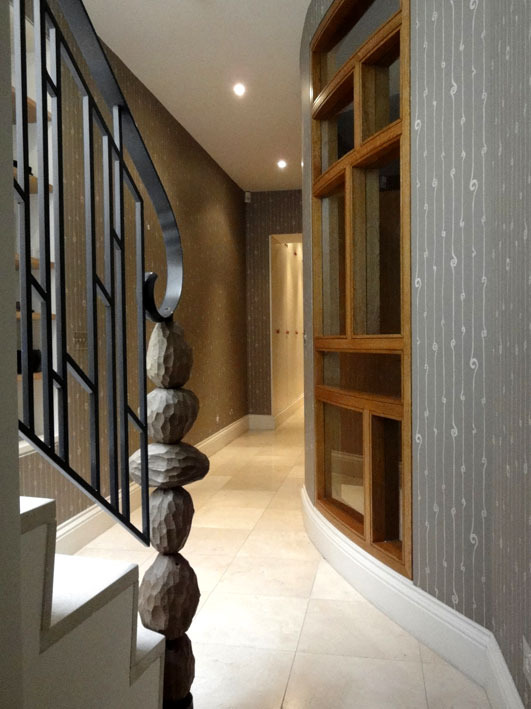 BASEMENT PASSAGE Another oak boulder newel-post marks the foot of the stair, which gives onto a corridor running the depth of the house. I broke up the monotonous length of this by forming an elegantly curved bow-front to the big playroom/cinema, with natural oak-framed windows borrowing light.