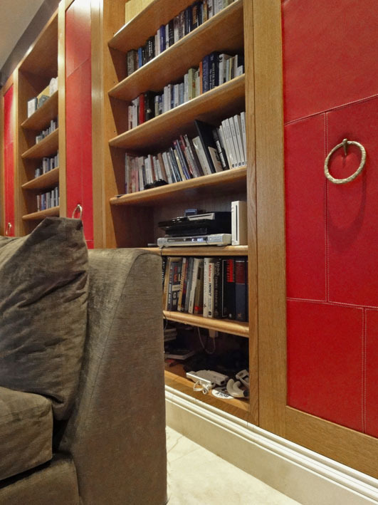 CINEMA / PLAYROOM A detail of the bookcases that fill one wall, in natural oak, the shelves broken up by cupboard doors covered in padded panels of stitched-together scarlet leather with polished brass versions of my Ring handle.