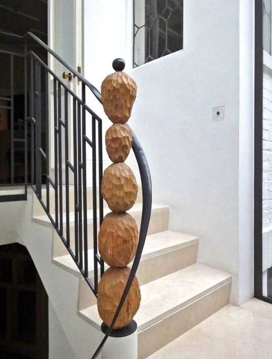 NEW STAIR I designed the balustrade in grey steel to complement the original leaded window, with a sweeping curve of handrail elegantly wrapping around a playful newel-post of sculpted oak 'boulders': an organic, earthy counterpoint to Rolf's crystals and all that glass slickness. The 'boulders' are loose on a steel pole, so that you can spin them as you pass, like a giant toy.