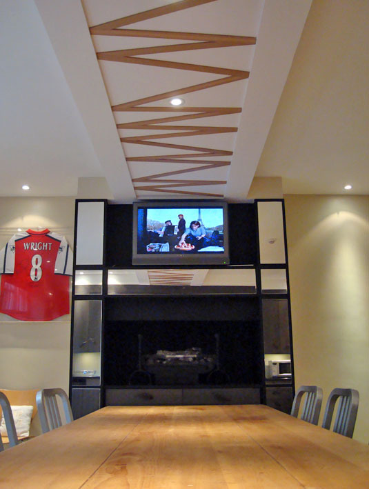 CHELSEA KITCHEN My sweet client is an avid Arsenal fan, hence the totemic red shirt. The rather ugly raised fireplace & television combination was already there; I framed it in sectional mirror to give it some lightness and elegance. Note the now-centred beam arrangement.