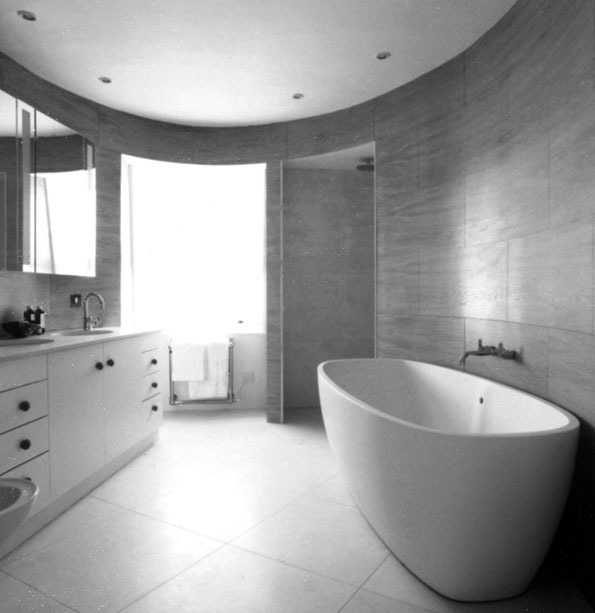 BATHROOM The flat originally had just one mean, small bathroom. I persuaded the client to sacrifice a third bedroom in order to have a new bathroom of comfort and beauty. This I made oval, panelled in a blockwork of birch plywood, with a stone floor that continued into the walk-in shower.