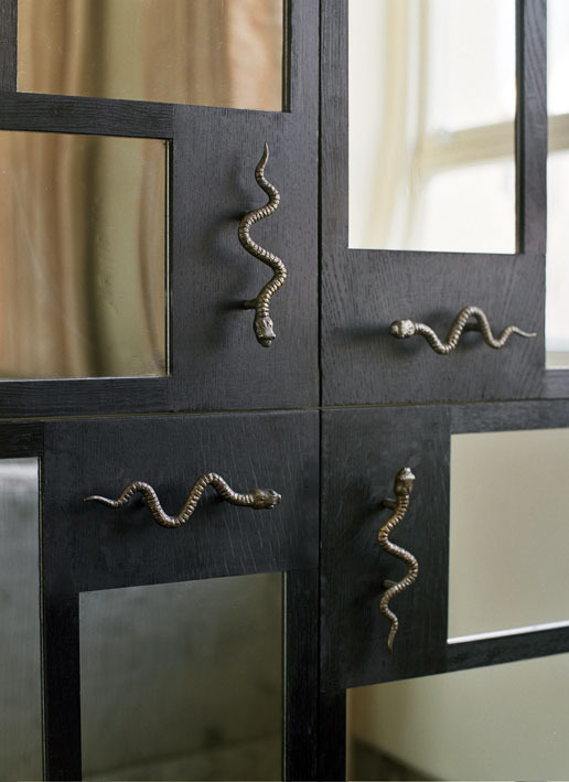 CUPBOARD DETAIL Four of my bronze snakes met at the centre of each mirrored cupboard, framed in black-stained oak.