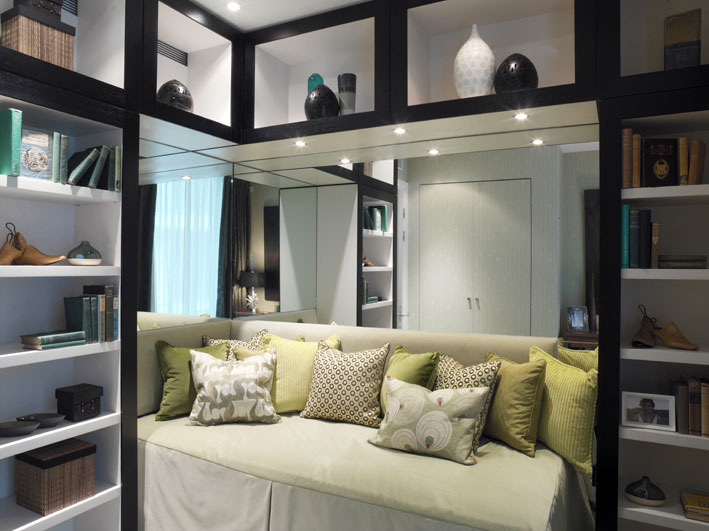 STUDY A small second bedroom was furnished to double as a study, with bookcases in black oak, lined with white lacquer, framing an eye-confounding mirrored alcove which held a daybed holding more bold-print cushions.
