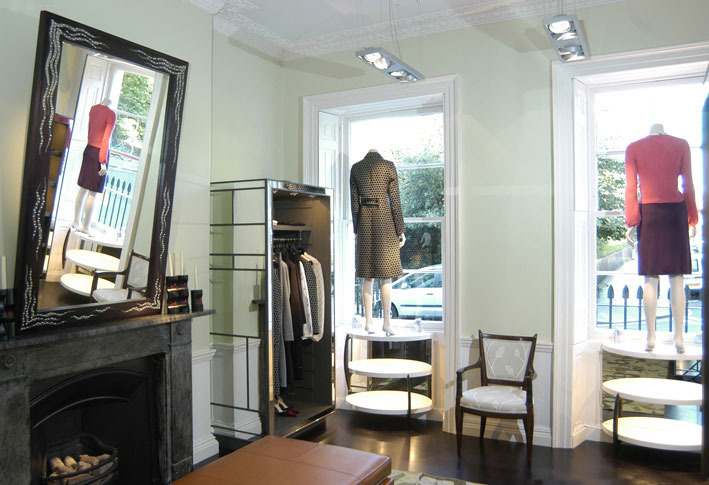 PONT STREET Allegra's second shop, on Pont Street, was the lower floors of a house, whose rooms, complete with plasterwork and fireplace, we had to retain. I furnished the spaces with freestanding display units in drab grey with inlaid strips and panels of mirror, giving them a touch of 30's glamour. Over the chimney is a black oak mirror frame that I decorated myself with silver paint and upholstery nails.