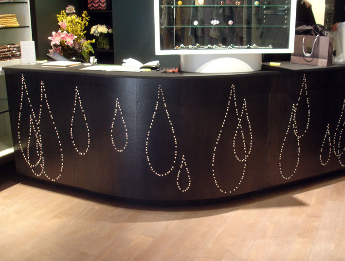 MADISON AVENUE The sales counter, with another design of falling drops in nickel upholstery nails on black oak.
