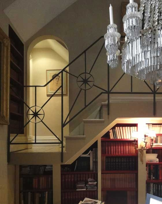 LIBRARY From the basement library, looking up at the stair. Through the arched doorway is a youthful self-portrait by the brilliant interior and set-designer Oliver Messel.