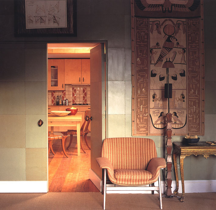 LIVING ROOM AND KITCHEN Looking through an open door painted with faux leather to the kitchen, which had a striped floor of alternating cherry and walnut boards. Beside it, an Egyptian patchwork hanging, a standard lamp designed by me with carved wooden blocks on a steel frame, a 60's Italian chair and an English gilt gesso table of 1730.