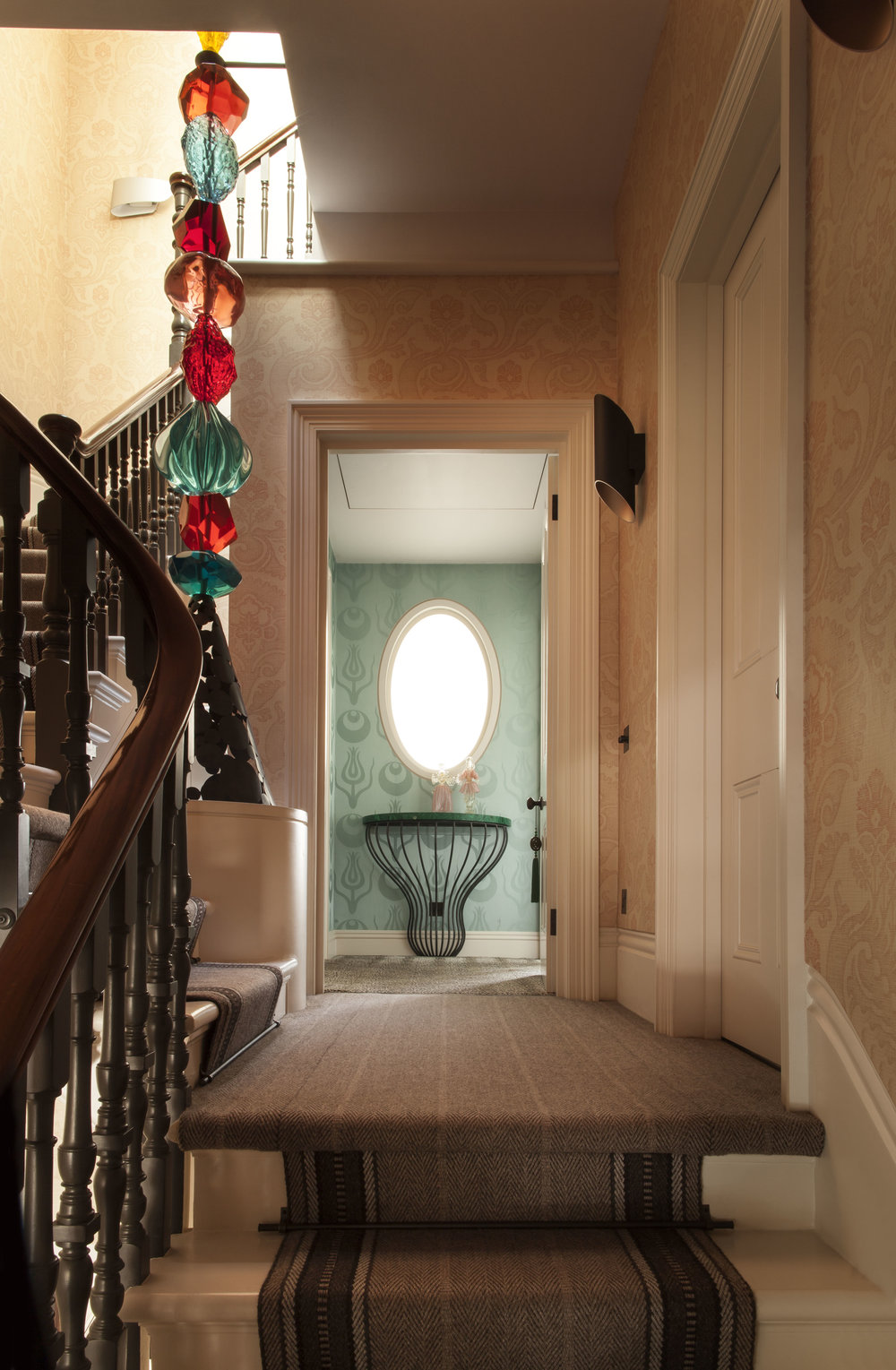 STAIRWAY Featuring Ashley's Cast-Resin Totem Sculpture as a banister and Ashley's custom Bargello-print wallpaper