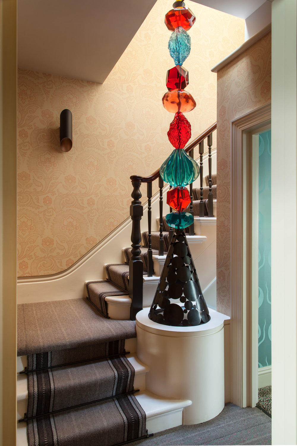 STAIRCASE Featuring Ashley's Cast-Resin Totem Sculpture as a banister and Ashley's custom Bargello-print wallpaper