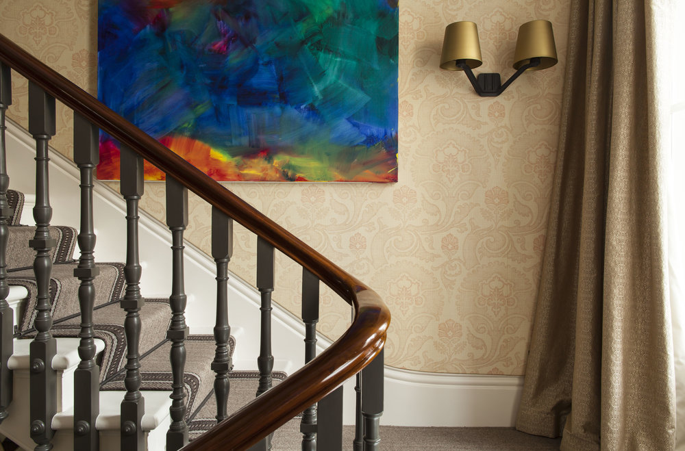 STAIRWELL DETAIL Featuring Ashley's custom Bargello-print wallpaper