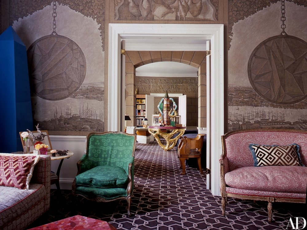 DRAWING ROOM   The London home of newlyweds Kata and Ashley Hicks showcases the latter's creative vision, from the living room's hand-painted mural of Constantinople to the chain-link-motif carpeting; Ashley also made the golden table in the mirrored bedroom niche beyond and the obelisk atop it.