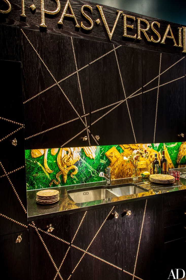 """KITCHEN   A client's admonition (""""This is Not Versailles"""") emblazons the kitchen; Ashley created the backsplash and studded the cabinets with brass nails."""