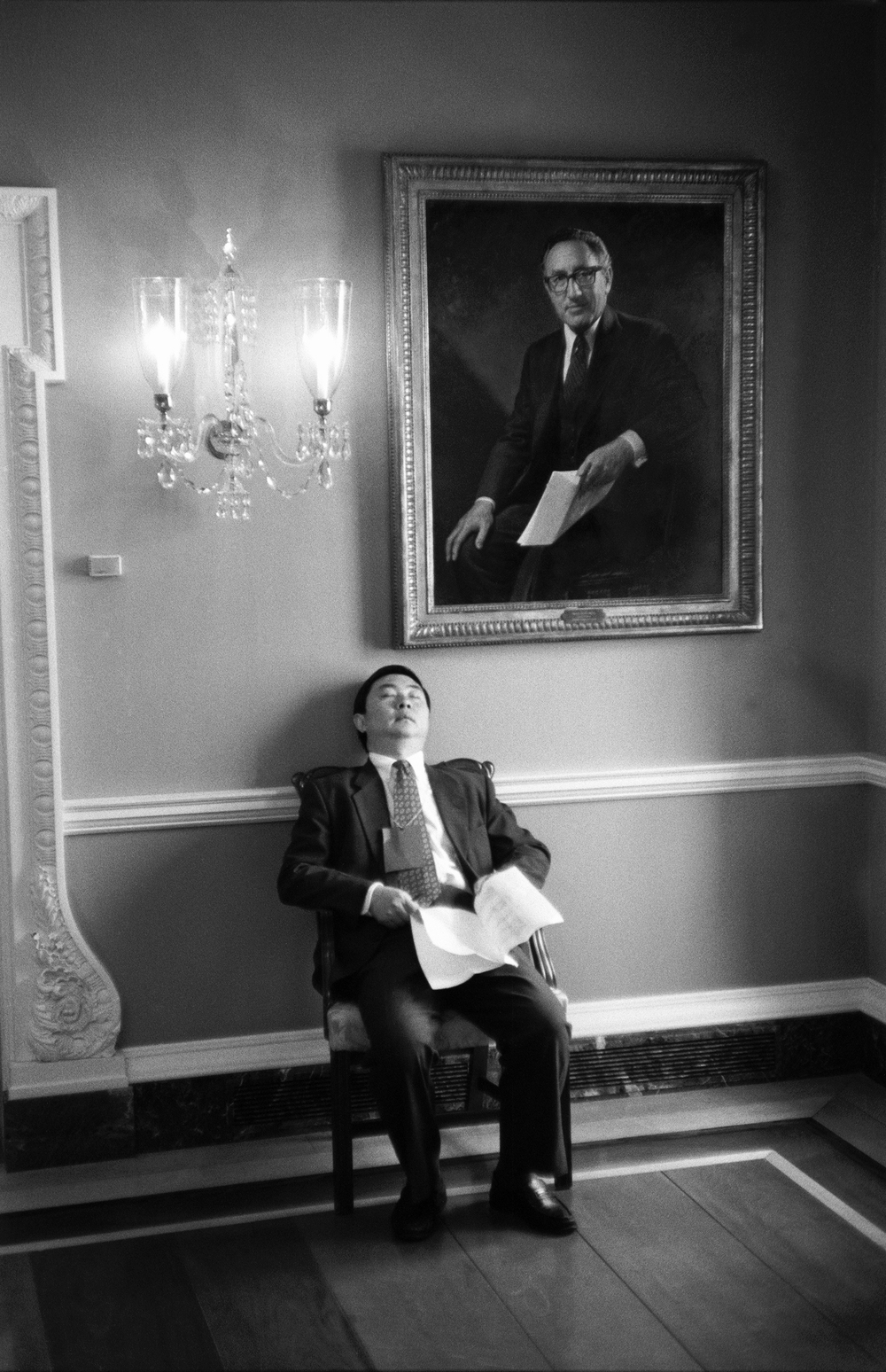 4.9.99--Washington, DC--A diplomatic aide snoozes under a portrait of Henry Kissinger at the State Department just 20 feet away from a joint press conference between Vice President Al Gore and The People's Republic of China's Premier Zhu Rongji.