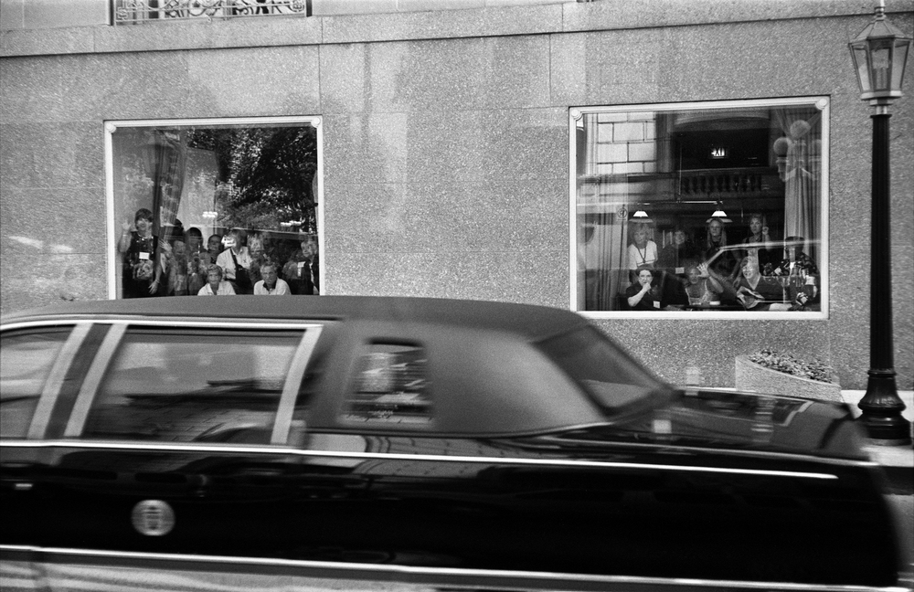 6.30.99--Chicago, IL--Onlookers inside the Sheraton Hotel catch a quick glimpse of the Presidential limousine as it speeds by en route to the airport.
