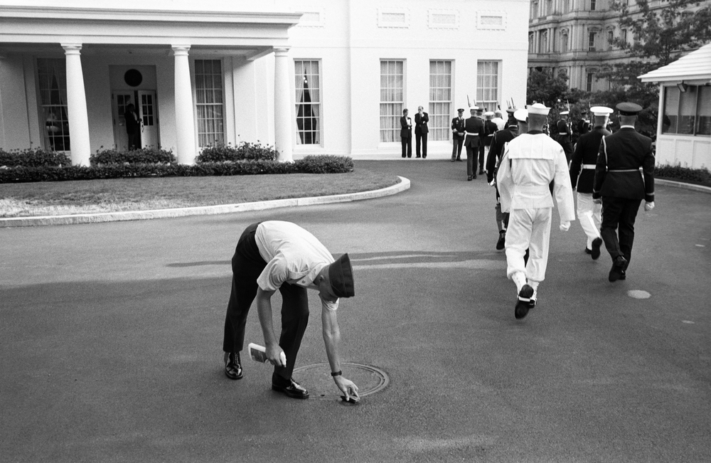 "7.14.99--Washington, DC--A designated member of the Honor Guard Detail adheres to the ""leave no trace"" policy at the White House by removing chalk place-markers in the driveway after an event for a visiting dignitary."