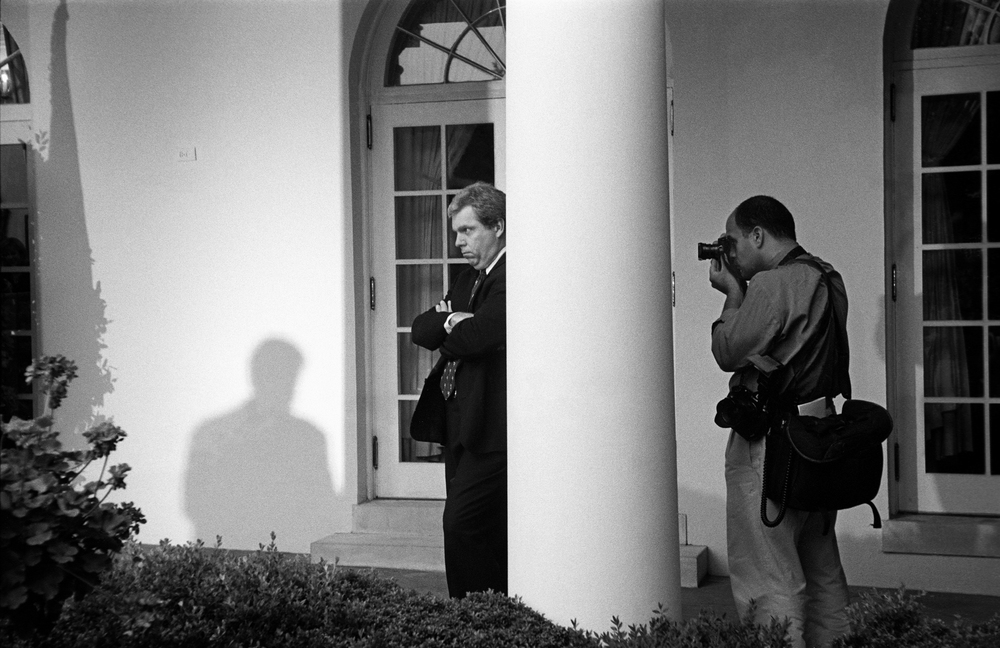 7.27.99--Washington, DC--White House photographer Ralph Alswang photographs Press Secretary Joe Lockhart watching President Bill Clinton during a news conference in the Rose Garden.