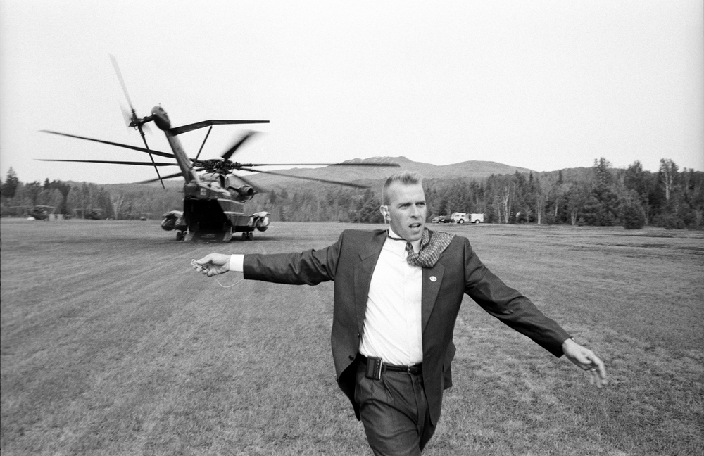 10.8.99--Mont Tremblant, Quebéc--An agent directs the Press Corps to the waiting helicopter after a long day at the Forum of Federations Conference.