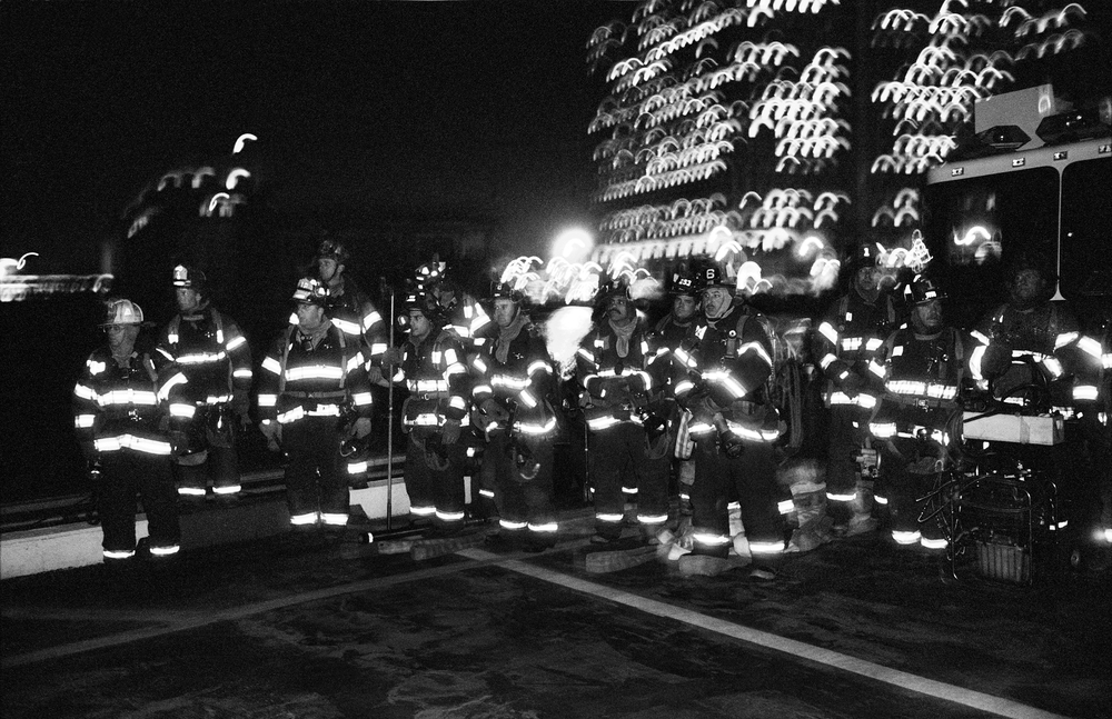 10.25.99--New York, NY--On duty for the President's arrival via Marine One, members of the New York Fire Department wait at the Wall Street landing zone.