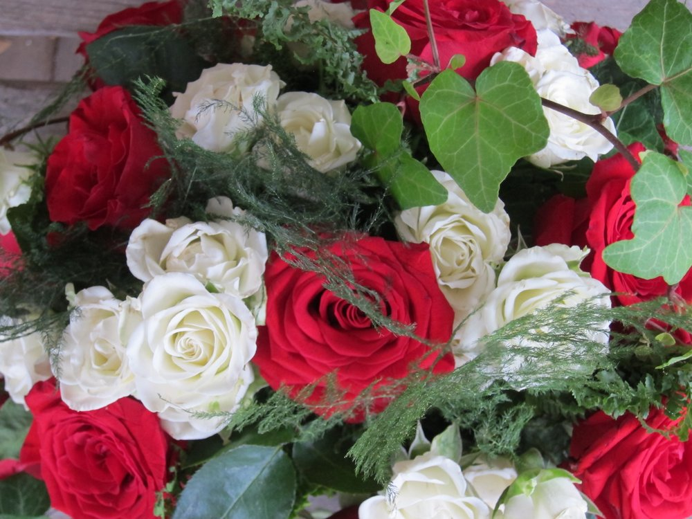 LOW CENTERPIECE of large red roses is embraced by small white spray roses, ivy and ferns. Many flower options available. Small round centerpiece is $39. Medium oval is $49.