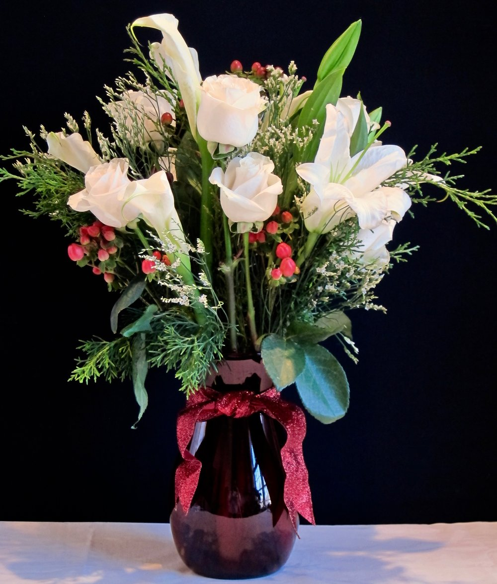 WINTER WHITE DOZEN features a bouquet of  roses, lilies and hypericum berries with seasonal foliage, $75.