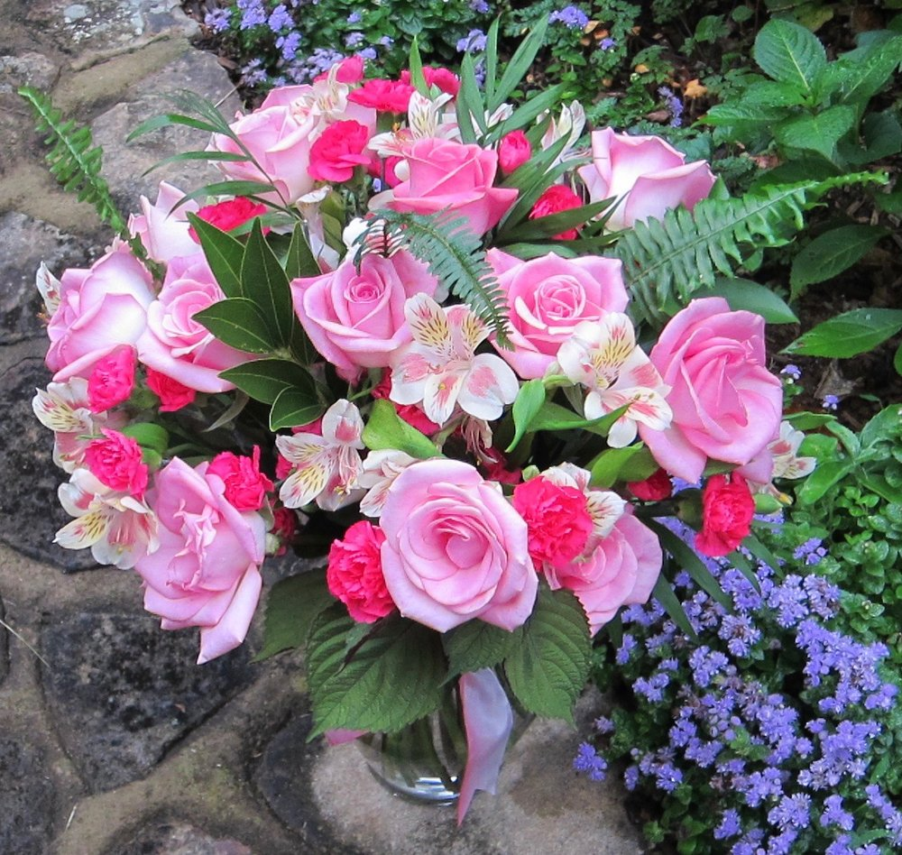 IN THE PINK dozen roses with hot pink mini carnations, alstroemeria and mixed foliages in a glass vase for $75.