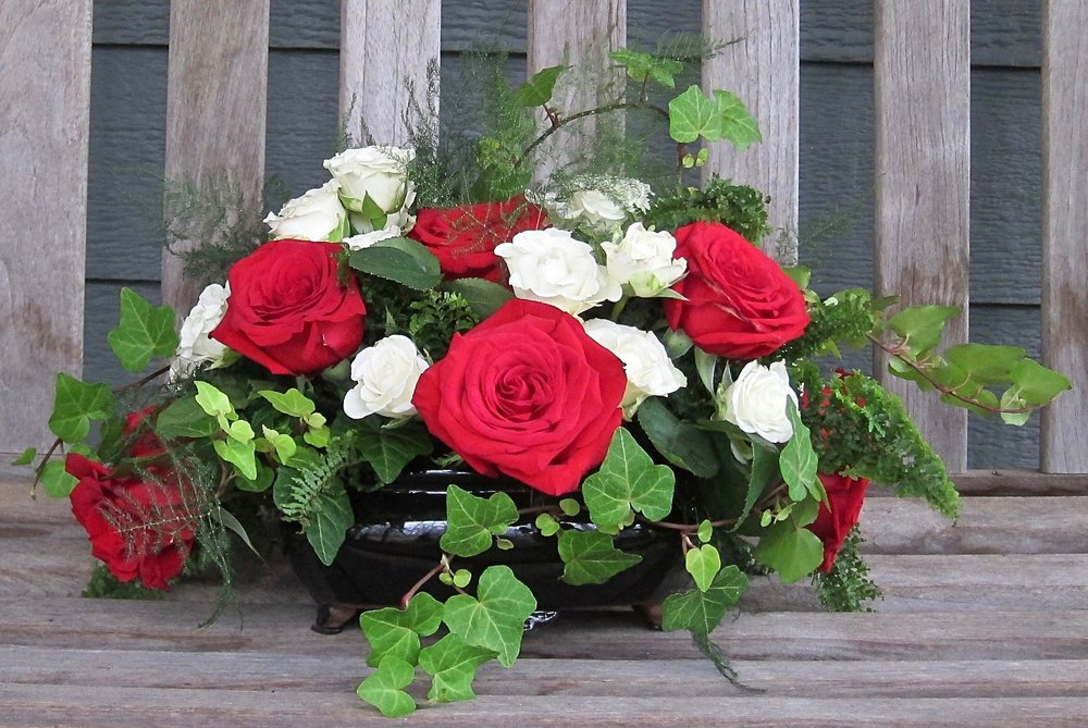 LOW ARRANGEMENT of large red roses and small spray roses, from $45.
