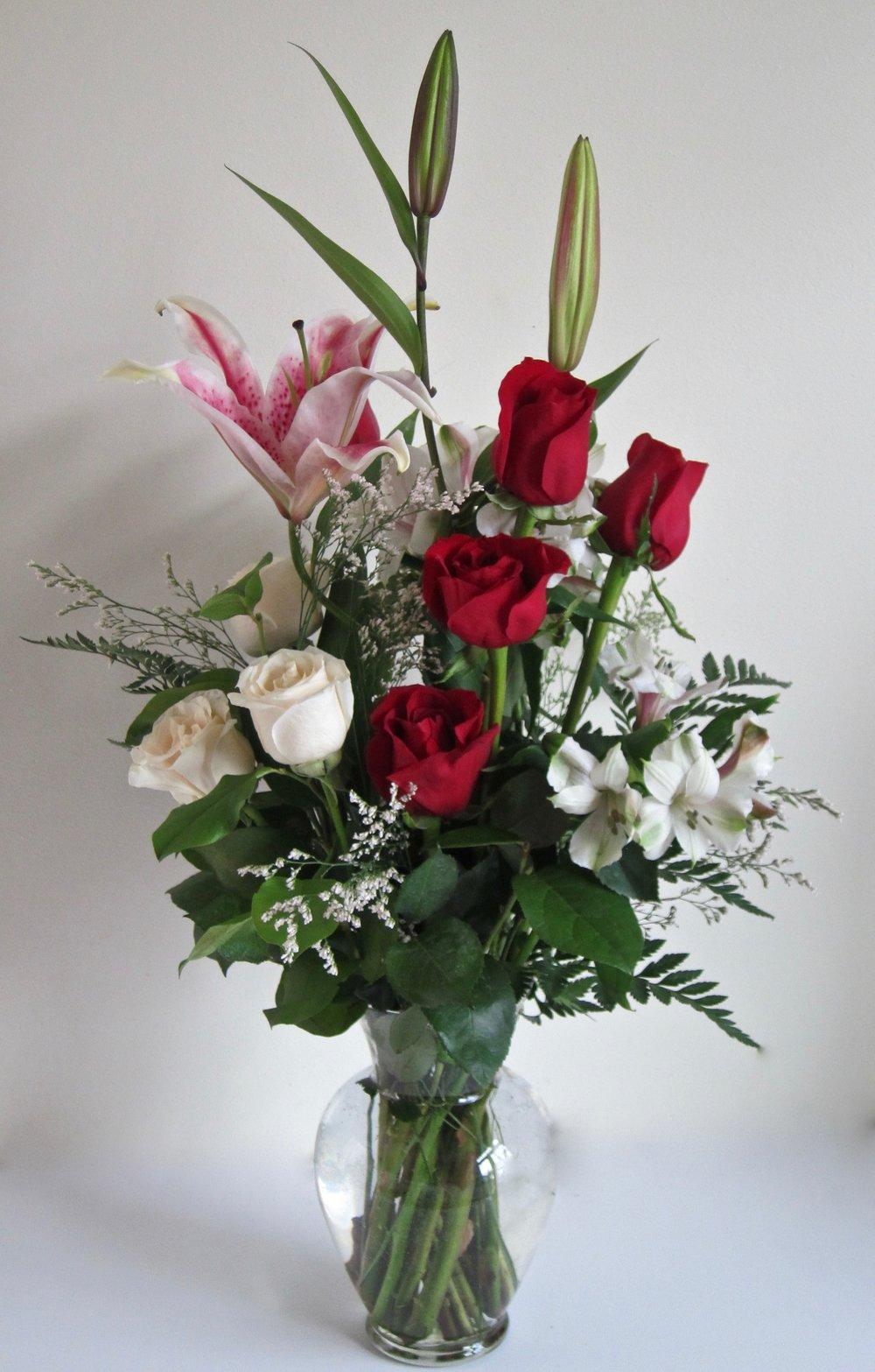 STAR LILIES AND ROSES pair nicely in a tall bouquet.  Half dozen roses mixed with other flowers for $55.