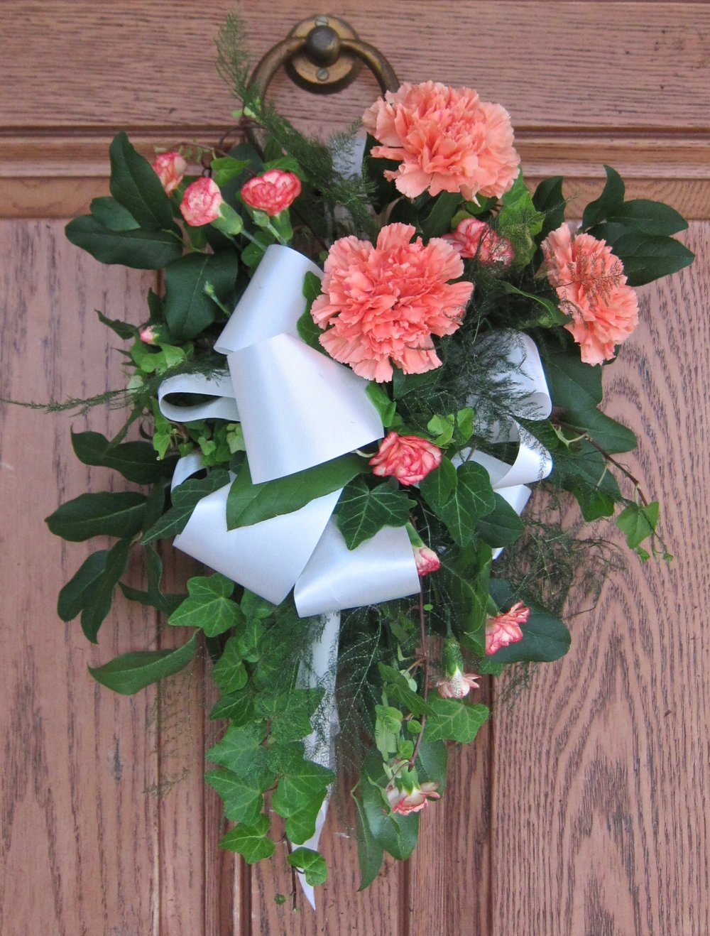PEW BOUQUET OF mini and large carnations with ivy and ferns.