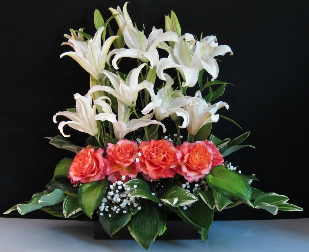 TALL PARALLEL Lilies with a base of large flowers and foliages can be done in many color combinations for an interesting one-sided altar arrangement, $75.