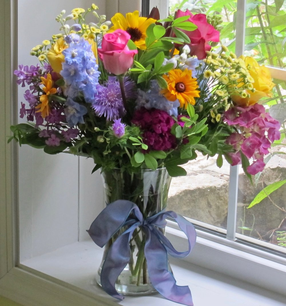 GARDEN BOUQUET   Summer colors in our tall gathering vase,  $55, premium flowers, $75.