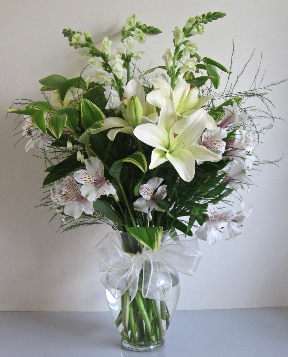 WHITE BOUQUET of lilies, snapdragons and ferns, $55.