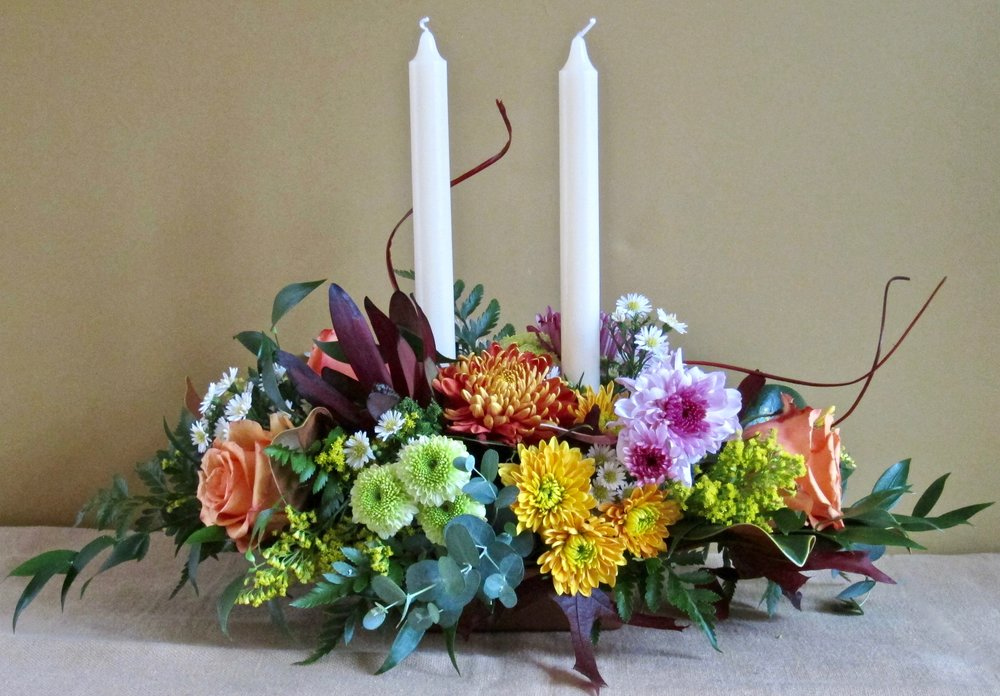 """FALL OVAL CENTERPIECE, 18"""" long by 8"""" high,$60 with two 10 inch ivory candles. Without candles, $55."""
