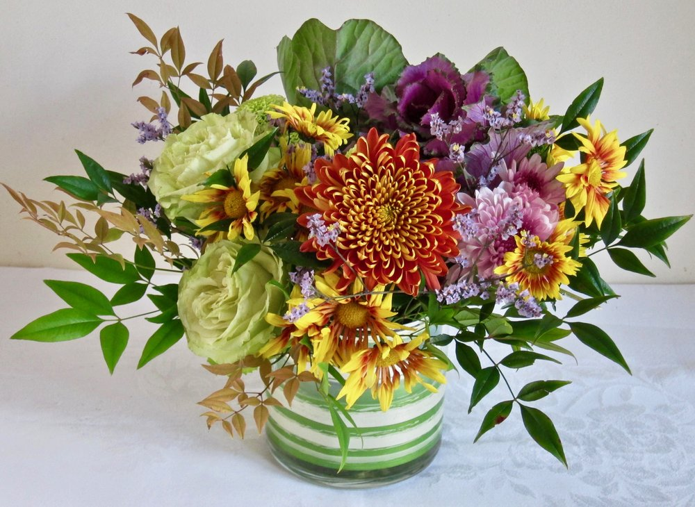 GLASS CYLINDER CENTERPIECE Clear of leaf-lined vase of seasonal flowers, $55.