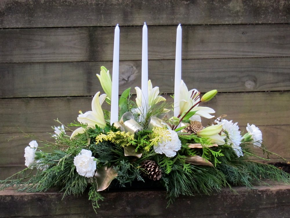OVAL CENTERPIECE of fresh greens, flowers, ribbon and candles, 20 inches long by 8 inches high. Add white, red or silver taper candles and ribbon, $60.