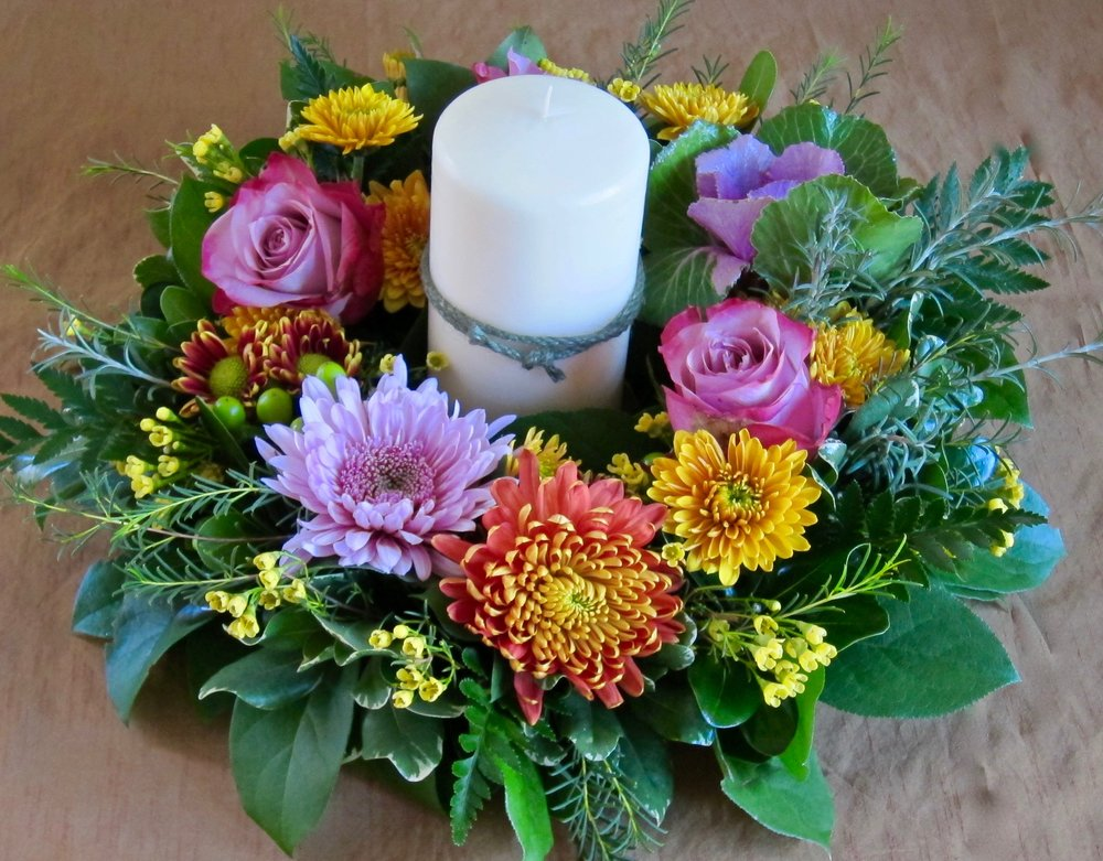CENTERPIECE WREATH of seasonal flowers with 6 inch pillar candle, $65.