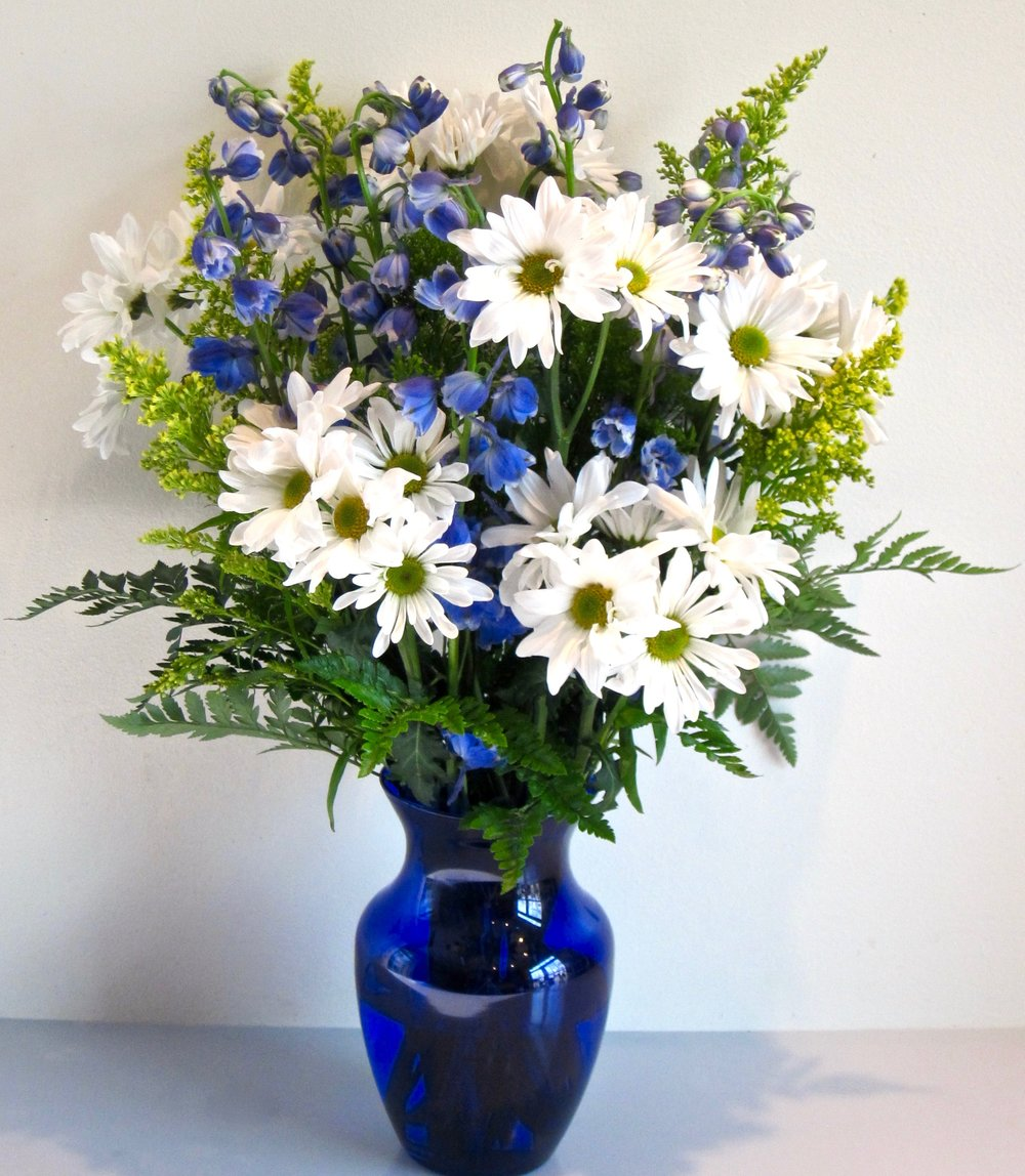 LAZY DAISIES   Blue delphinium and yellow solidago in a blue vase,  $50.