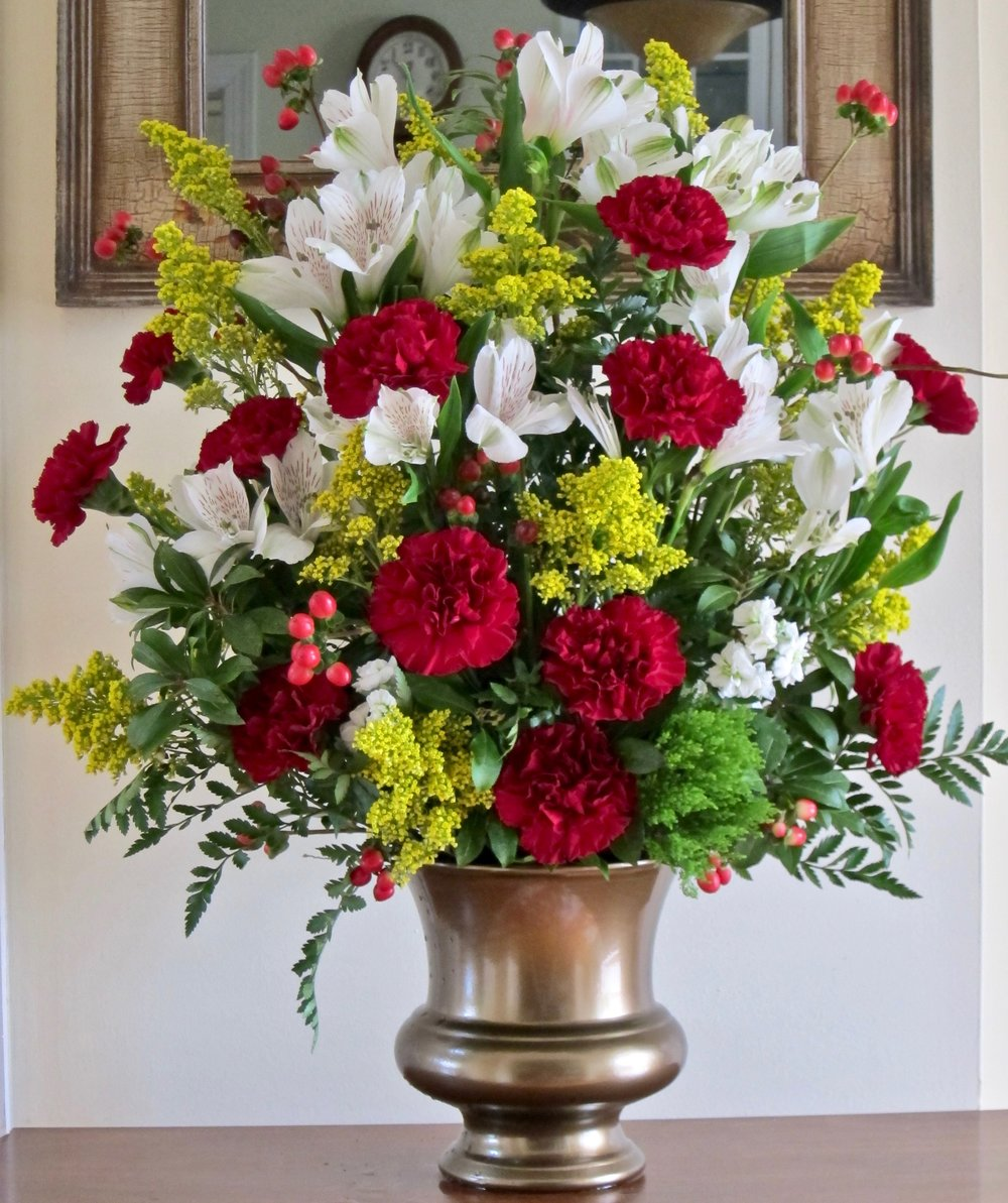 TALL CENTERPIECE Great for a side table, this one-sided arrangement can be custom designed in your container or ours, starting at $65.
