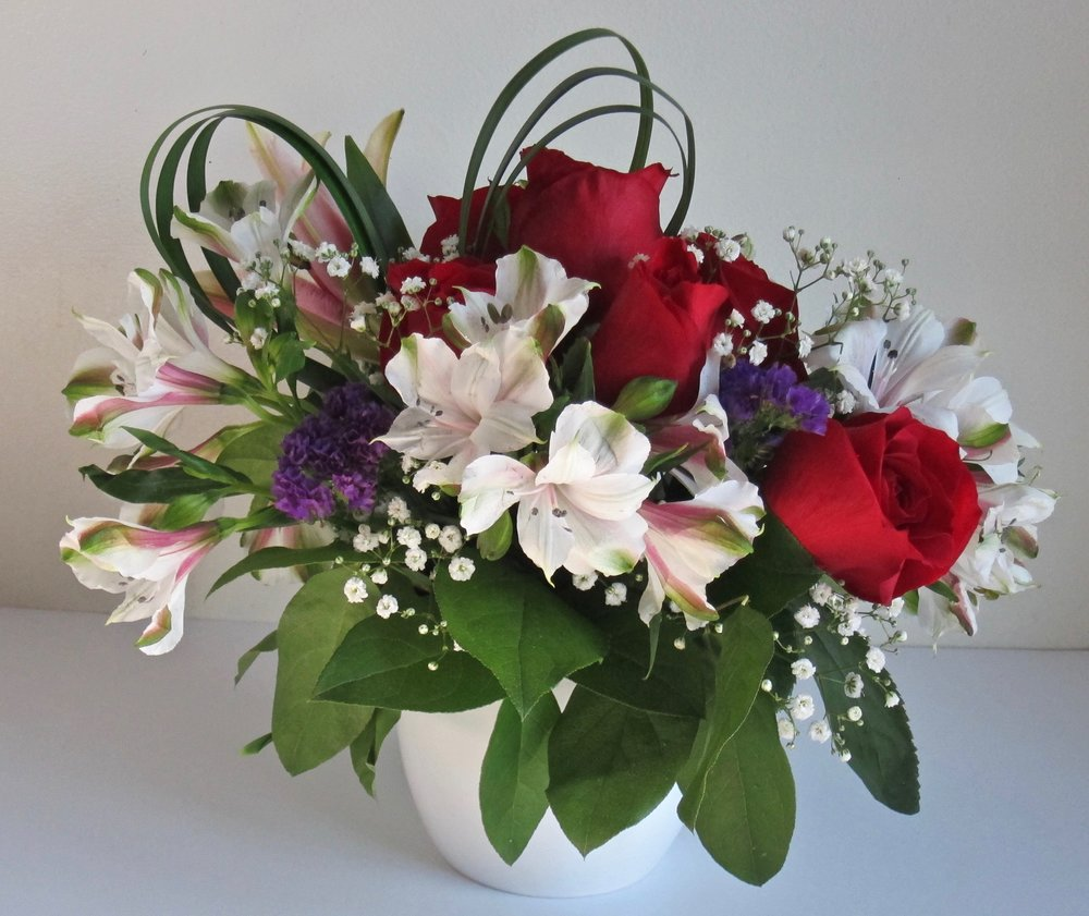 BIG HEART    Half dozen roses and white alstromeria, highlighted with baby's breath, purple statis and heart-shape foliage in a petite ceramic vase, $45. Other color combiniations can be substituted.