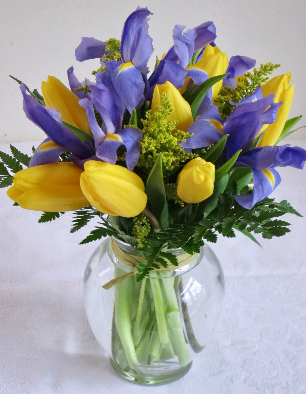 SHORT AND SWEET Iris and tulips accented with solidago in a low ginger vase, $40.