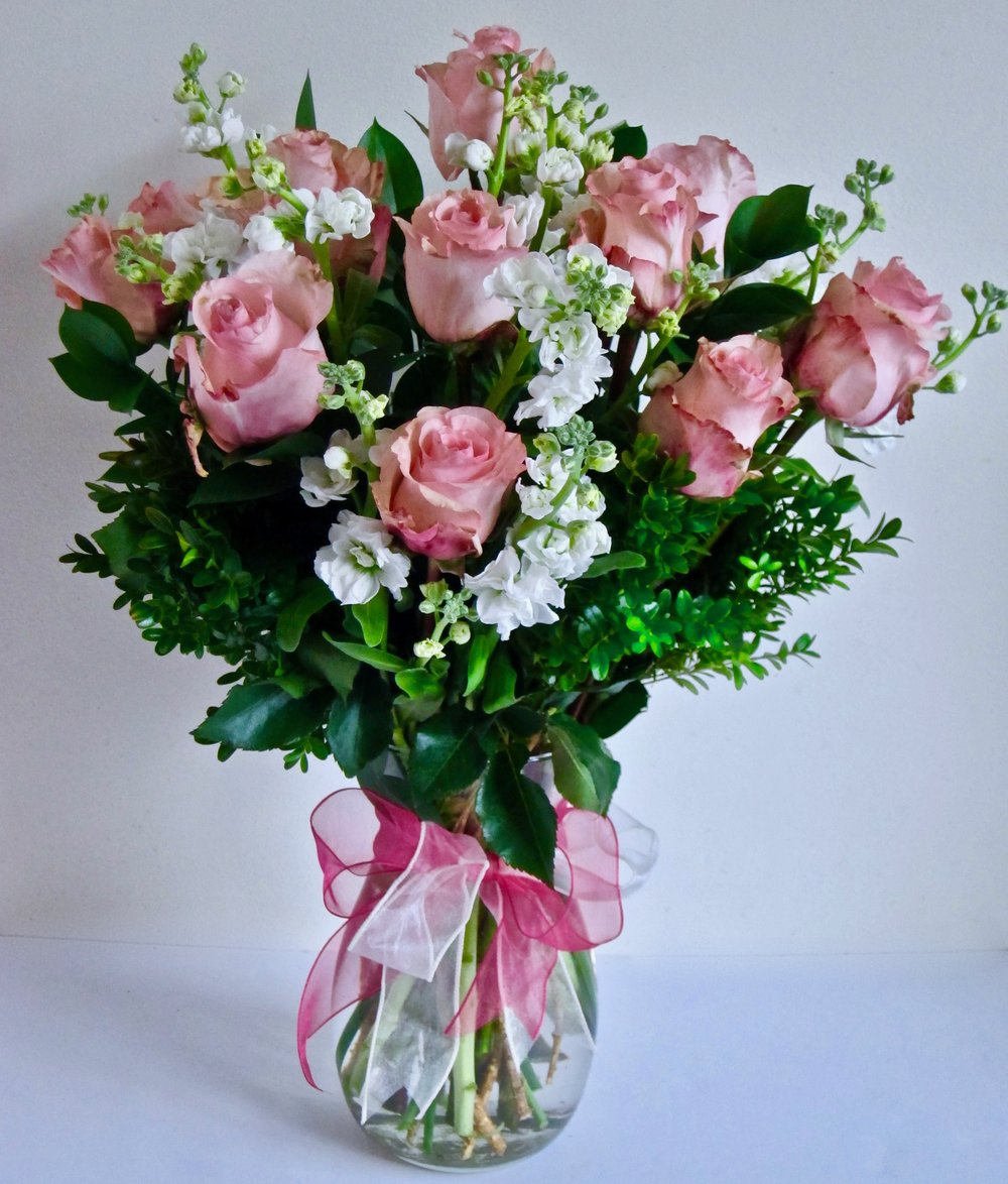 ROMANTIC Dozen large roses combined with fragrant spray stock and lush foliage, $75.