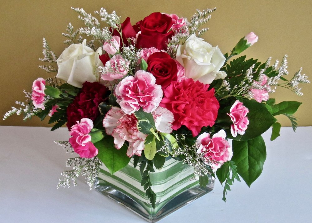 GLASS CUBE CENTERPIECE   Clear or leaf-lined vase of seasonal flowers,   $55.