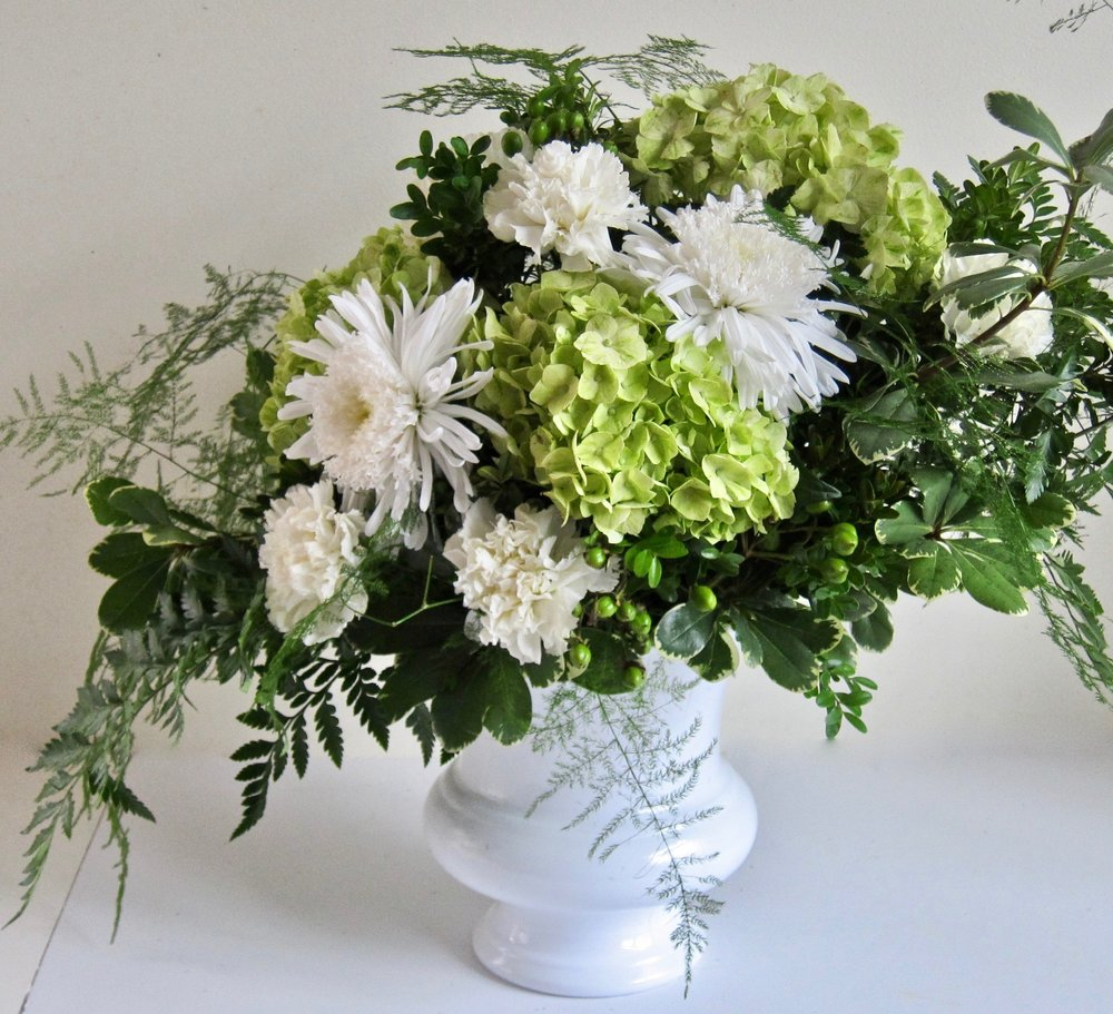 SIMPLE ELEGANCE    Created     with greens and whites in this centerpiece of h  ydrangeas, cremons and carnations accented with lush ferns and other foliages in a white urn, $65.