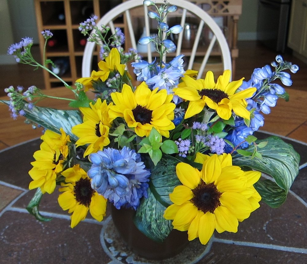 MOCHA LATTE   Wake up, cheer up with yellow sunflowers and blue delphinium in a mocha ceramic vase, $40.