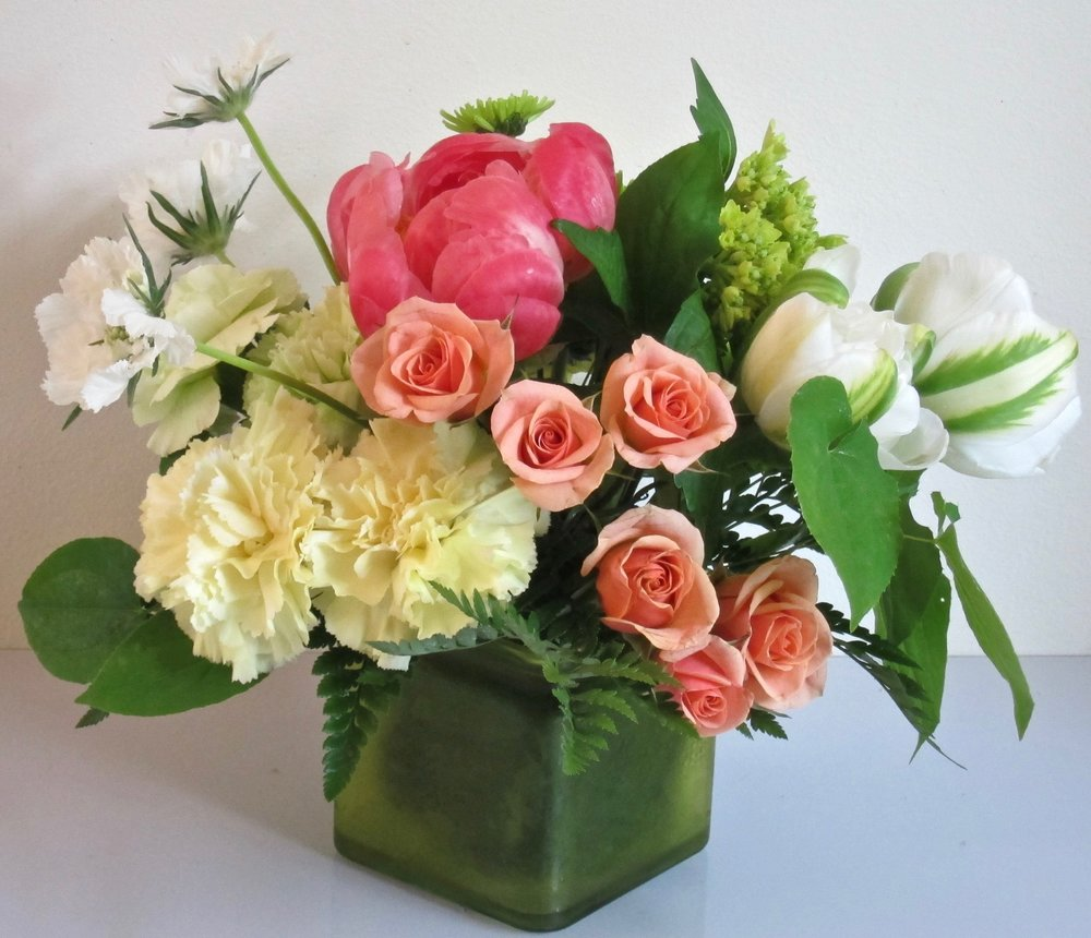 PEACHES AND CREAMS   A medley of  peonies, parrot tulips, spray roses and other flowers in a low cube or cylinder vase, $55.