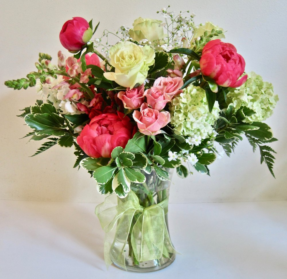 PEPPERMINT   Carnations, roses and lilies with fragrant waxflower and evergreens,  $4o.