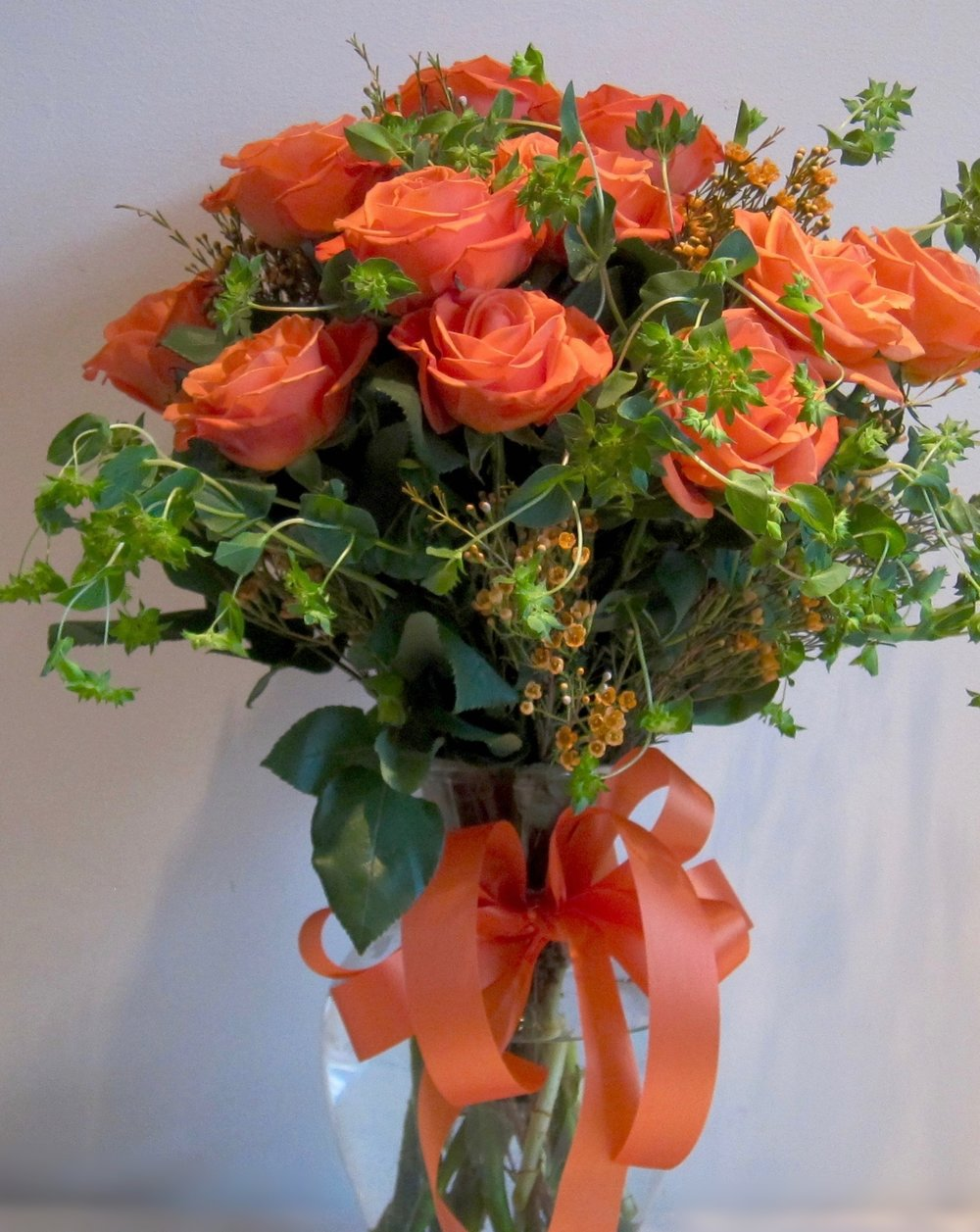 CASUAL ROSES   A dozen arranged in a loose, casual style with waxflower and buplurem foliage. Allow next day delivery for the color of your choice, $65.
