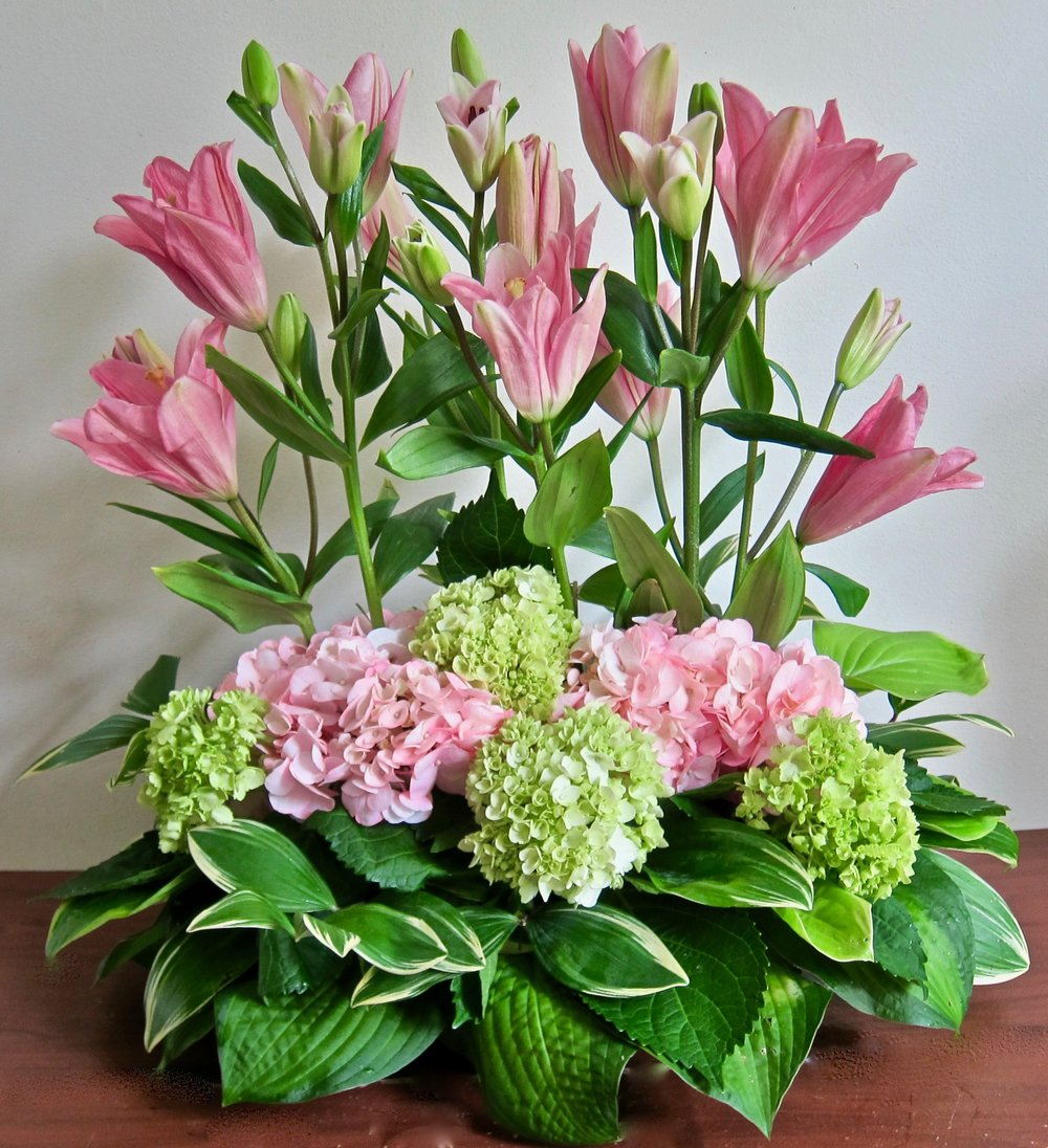 PARALLEL LILIES   With a base of hydrangeas and foliages can be done in many color combinations for an interesting one-sided arrangement,  $75.